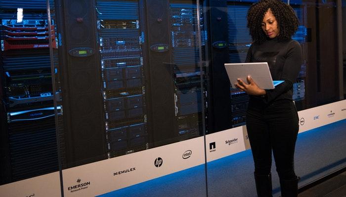 Imagem de uma mulher trabalhando próxima de servidores, representando um serviço de hospedagem de sites.