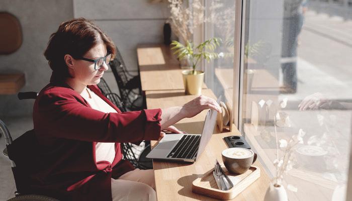 Mulher mexe em computador em café, como quem lê uma newsletter