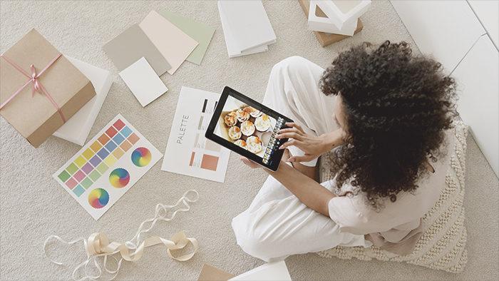 Mulher sentada no chão escolhendo as fotos da sua loja para representar como montar um ecommerce.