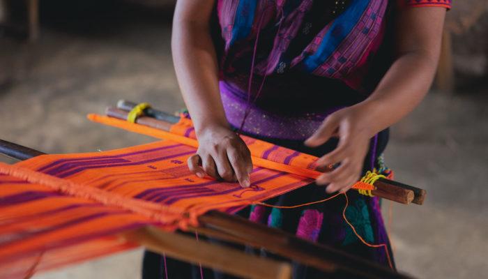 mujer tejiendo con telar de cintura