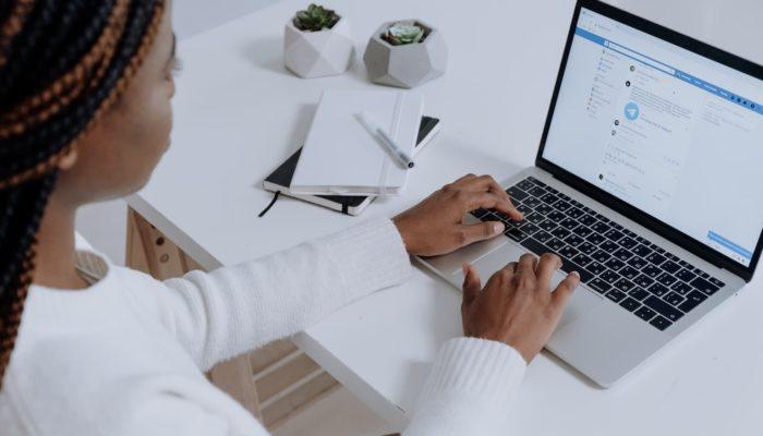 Mujer abre su cuenta de facebook en laptop mesa blanca con dos plantas pequeñas