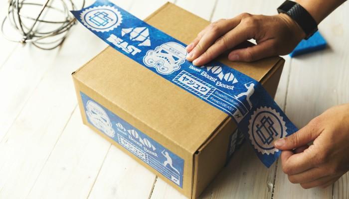 Pessoa cola etiqueta em caixa, representando o dropshipping no Mercado Livre