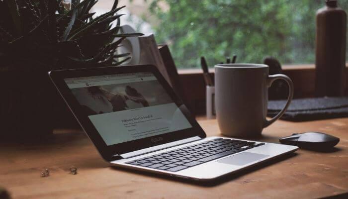 imagem de um computado aberto, com uma xícara de café ao lado. Dispositivo é essencial para criar textos de copywriting