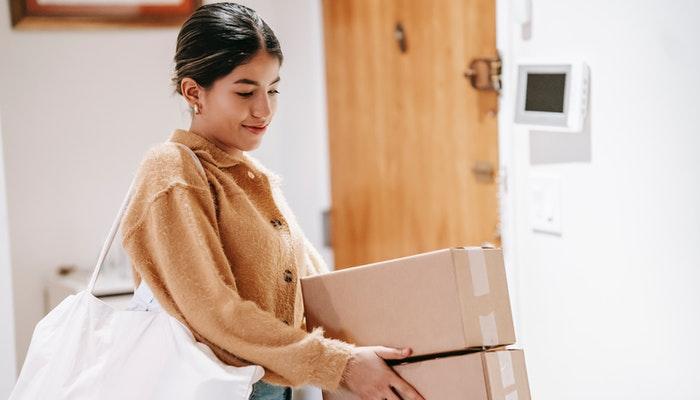 Mulher segura caixas que serão enviadas pelo Sedex Hoje