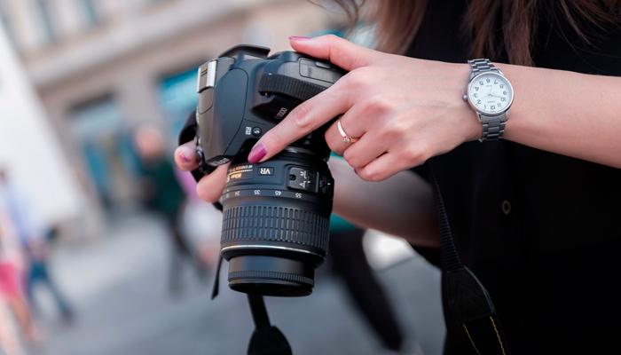 Mulher segurando câmera fotográfica, como as vendidas pela F&F Equipamentos Fotográficos.
