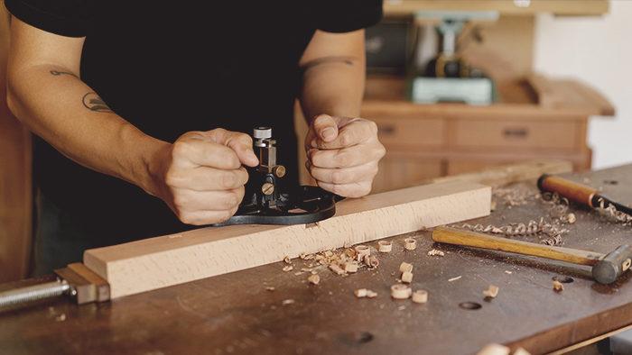 Imagem de um homem criando seu artesanato para vender com madeira.