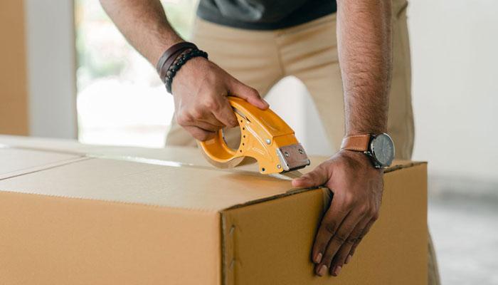 Close de mãos embalando uma encomenda para o dropshipping Shopee