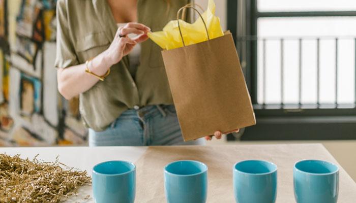 Mulher ajeitando embalagens sustentáveis para enviar produtos