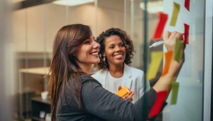 Duas mulheres escolhendo nome de loja para dropshipping usando post-its
