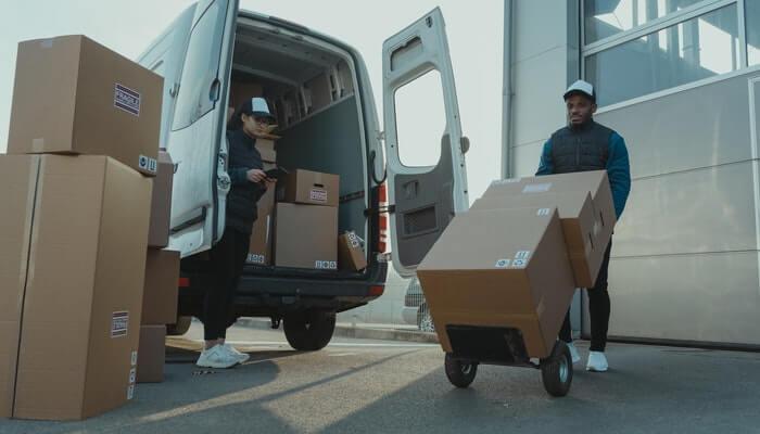 Homens carregando caixas representando o que é logística